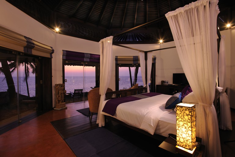 A four-poster bed with a view out to the ocean in a hotel room at Niraamaya Surya Samudra