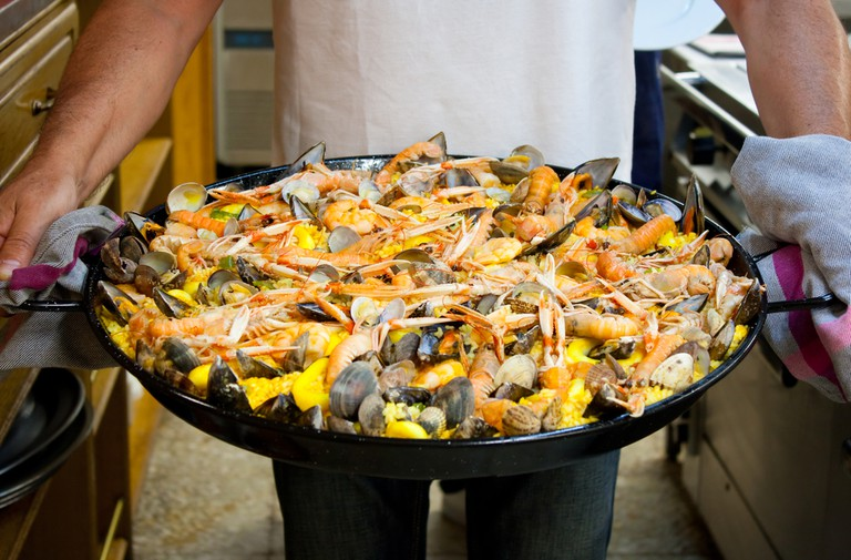 Carrying a freshly made seafood paella cooked in a basque gastronomic society San Sebastian