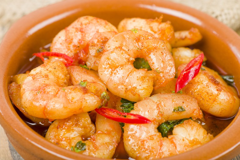 Gambas Pil Pil (Sizzling prawns with chili and garlic).