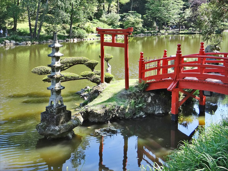 One of the garden's many traditional red Japanese bridges