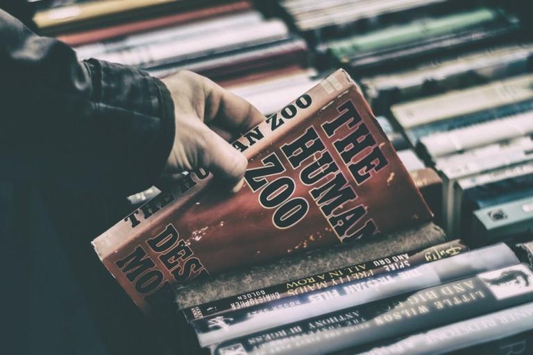 Man picking up a book