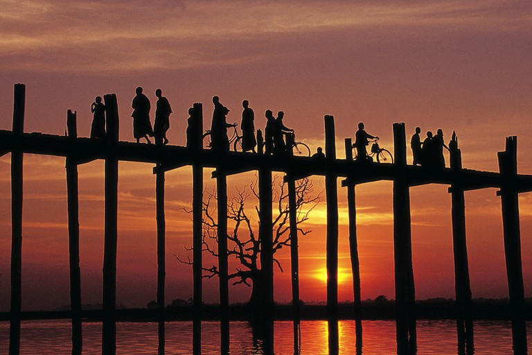 Silhouettes of people walking across U Bein Bridge at sunset