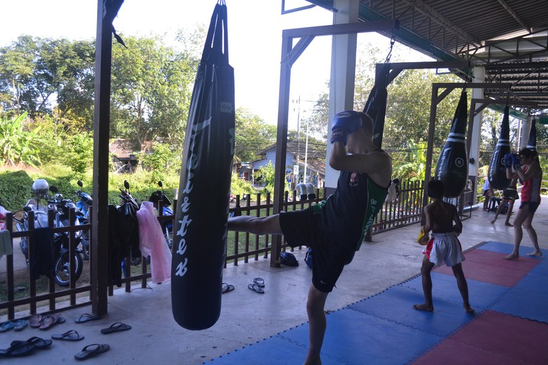 Children and adults practicing in a Muay Thai gym