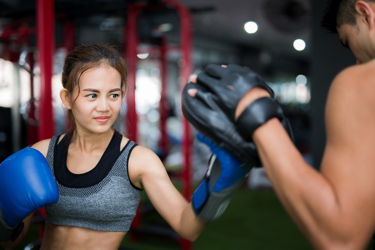 Young woman doing pad work in a Muay Thai gym