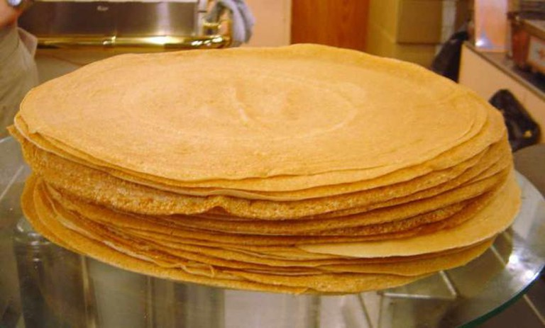 A steaming pile of crepes, ready to be filled