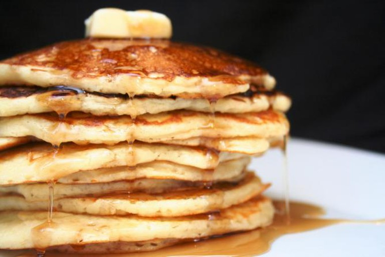 A stack of Buttermilk Pancakes with butter and syrup