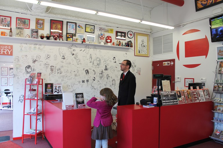 An owner of Challenger Comics with young girl