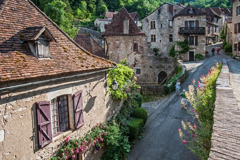 Tourists walking through the medieval village Saint-Cirq-Lapopie, Lot, Midi-Pyrenees