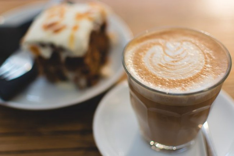 Flat white coffee and a slice of cake