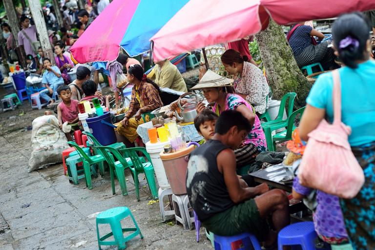 Food stalls under bright umbrellas line a marketplace in Yangon