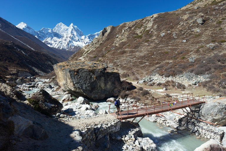 A trekker crosses a bridge on Pheriche Pass in the Sagarmatha National Park in Nepal