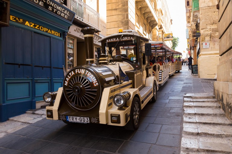 Tourist sightseeing train / trains running in the narrow streets and roads of the historic old city centre of Valletta, Malta. Island of Malta. (91)