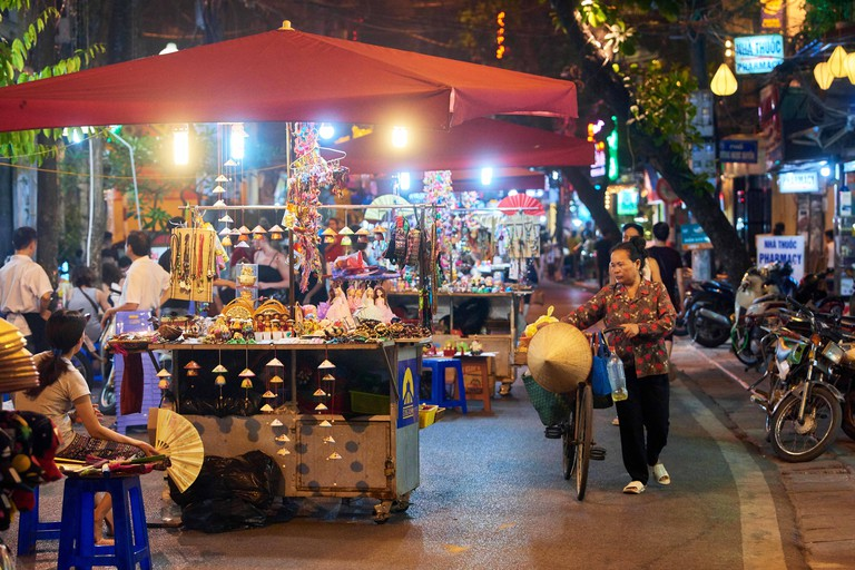 Night shot of one of the many busy streets that comprise Hanoi's Night Market in the Old Quarter, Vietnam. The popular market takes place on weekend e