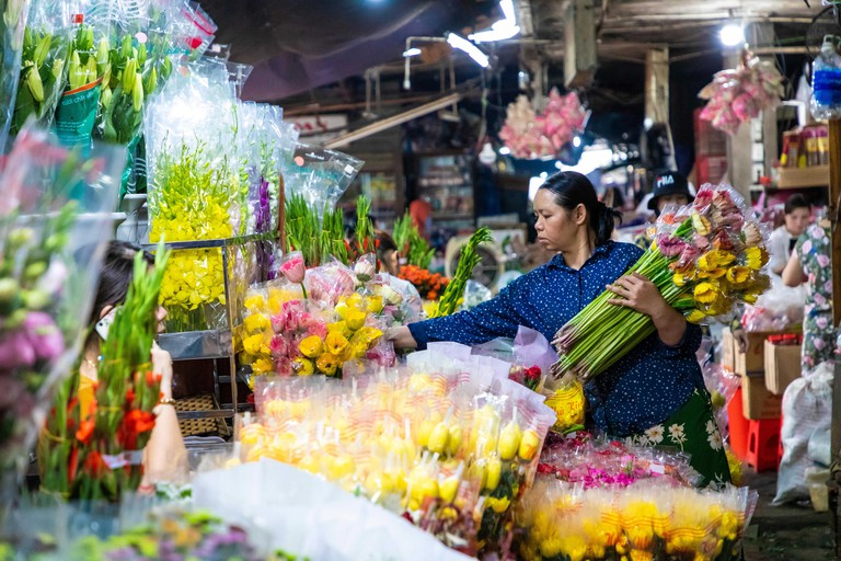 HUE, VIETNAM - NOVEMBER 19,2018: Sellers on the local market in Vietnam. Fresh flowers on traditional market.