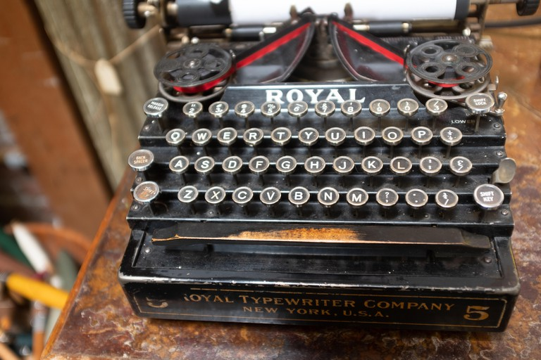 A close up of a vintage Royal typewriter showing signs of age on a wooden desk