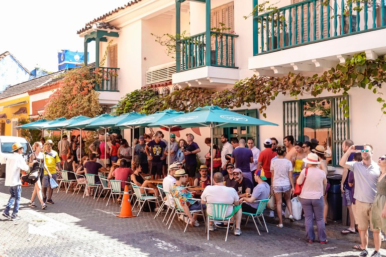 Cartagena Colombia Old Walled City Center centre Centro La Cevicheria popular restaurant alfresco tables umbrellas crowded busy man woman