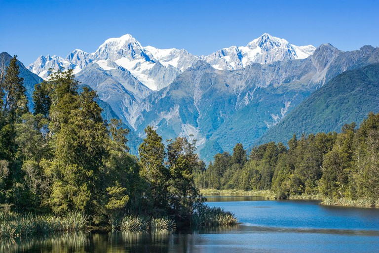 Lake Matheson with snow covered Mount Tasman and Mount Cook, New Zealand's highest mountain. Mount Cook is on the right.