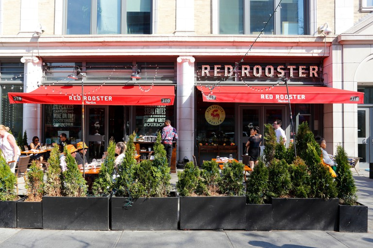 Red Rooster, 310 Malcolm X Blvd, New York, NY. exterior storefront of a soul food restaurant, and sidewalk cafe in Harlem, in Manhattan.