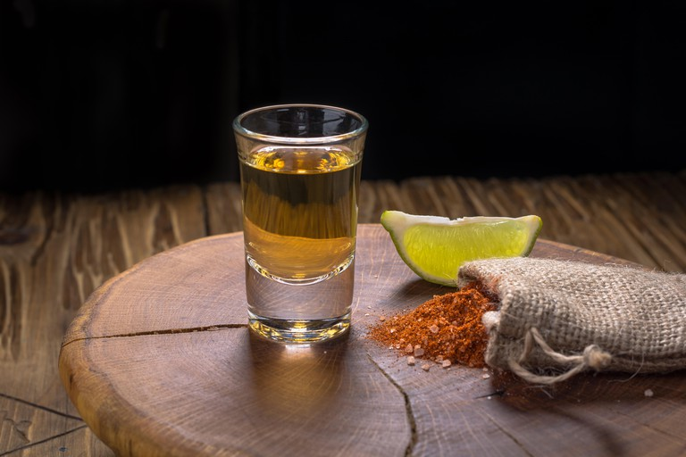 Mezcal shot with lime slices and worm salt. Mexican drink.