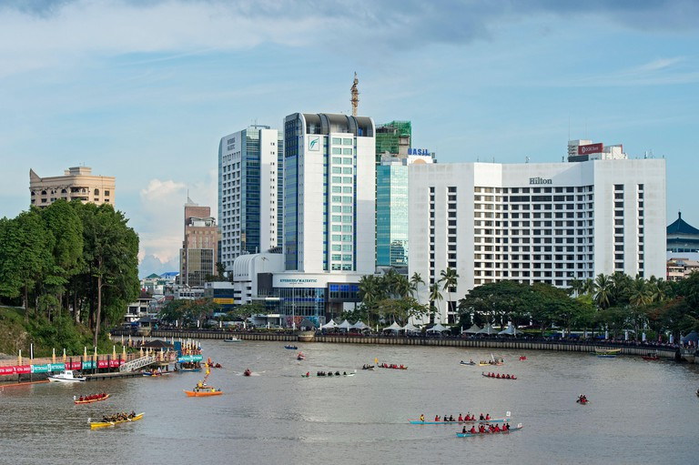 Kuching Waterfront with Hilton Hotel during Sarawak Regatta, on the Sarawak river, Kuching, Sarawak, Borneo, Malaysia