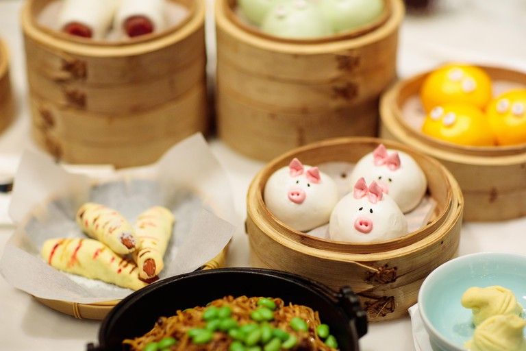 Dim sum, traditional Chinese dumpling in bamboo steamer, pig and animal theme for kids. Street food for children in China, Hong Kong. Family dinner wi