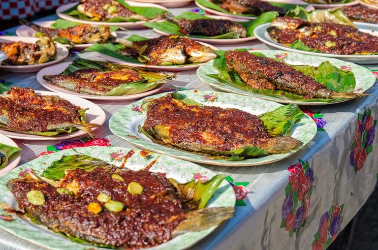 Grilled fish with spicy sauce on plate selling in Ramadan Bazaar Kuala Lumpur