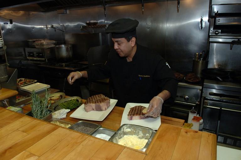 Chef prepares porterhouse steak at Ricardo Steak House in East Harlem in NYC