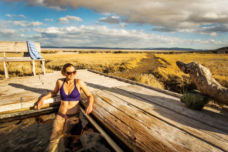 A young woman in a bikini sits in a natural hot spring tub surrounded by a vast marshy expanse under clouds and blue sky.