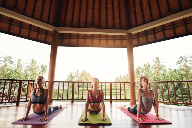 Three women doing the cobra pose yoga at class in Bali