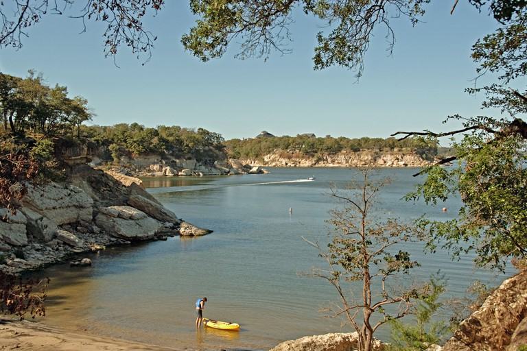 View of Lake Texoma at Eisenhower State Park outside Denison Texas and a man putting on his life vest to go kayaking.