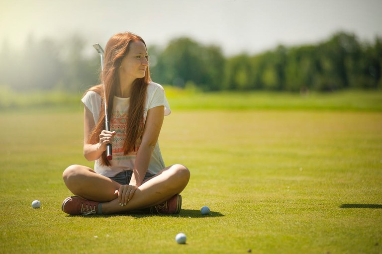 https://www.pexels.com/photo/woman-in-white-scoop-neck-shirt-and-blue-shorts-holding-a-golf-club-sitting-on-golf-field-1175023/
