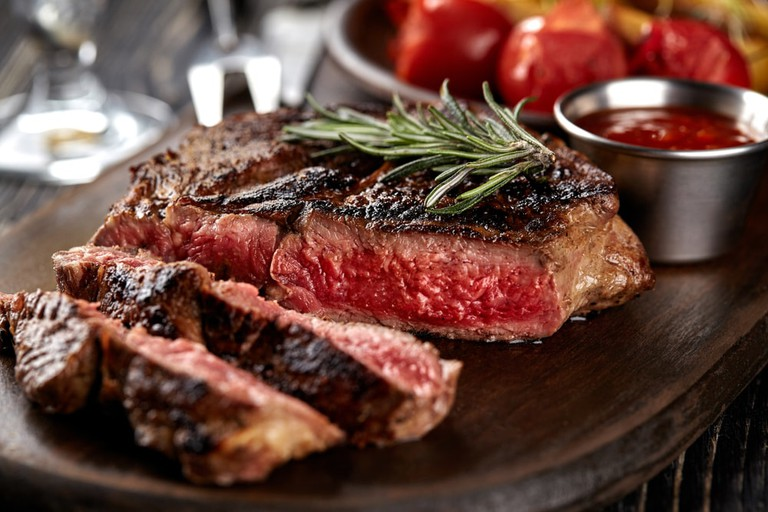 Juicy steak medium rare beef with spices on wooden board on table