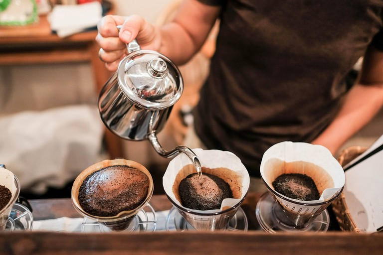 Man using drip brewing, filtered coffee.