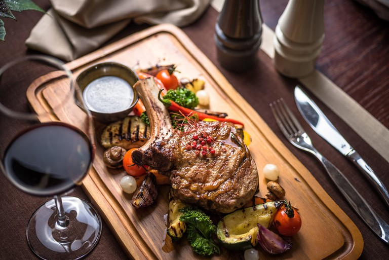Veal Tomahawk steak with onion marmalade, boletus sauce and grilled vegetables