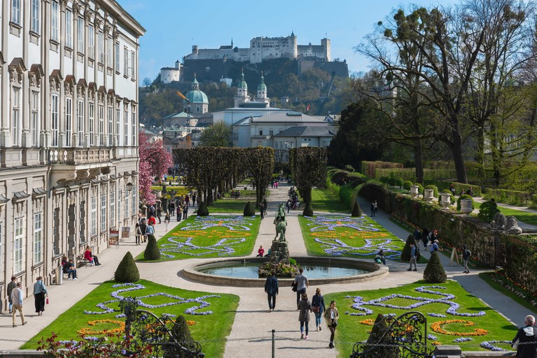 Schloss Mirabell, view across the Mirabell Palace Gardens (Mirabellgarten) towards the city cathedral and hill-top castle, Salzburg, Austria.