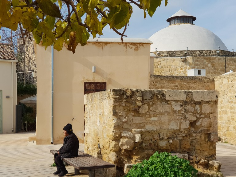 Nicosia, Cyprus - 19 January, 2019: A woman is resting on a bench outside the Omerye Hamam in the old town of Nicosia, Cyprus