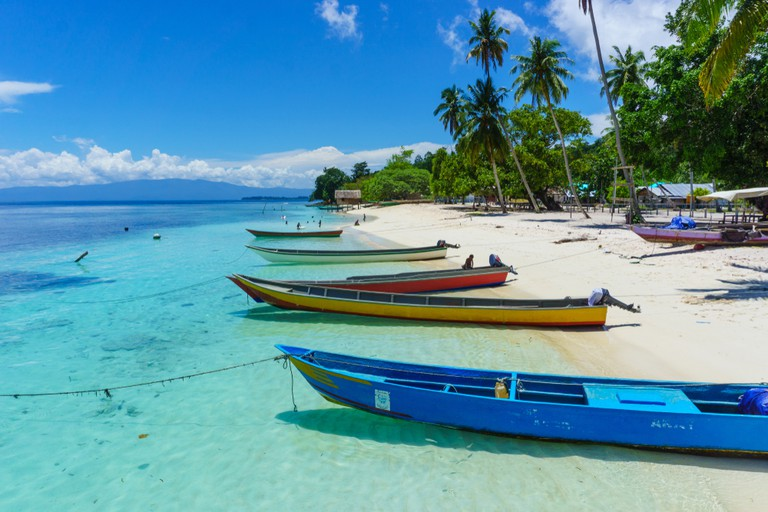 Wooden motor boats tied up on the beach, Raja Ampat Regency, West Papua, Indonesia.