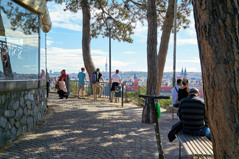 Tourists at the viewpoint at the Hanavsky Pavilion in Letna Park with a view of the Old Town of Prague