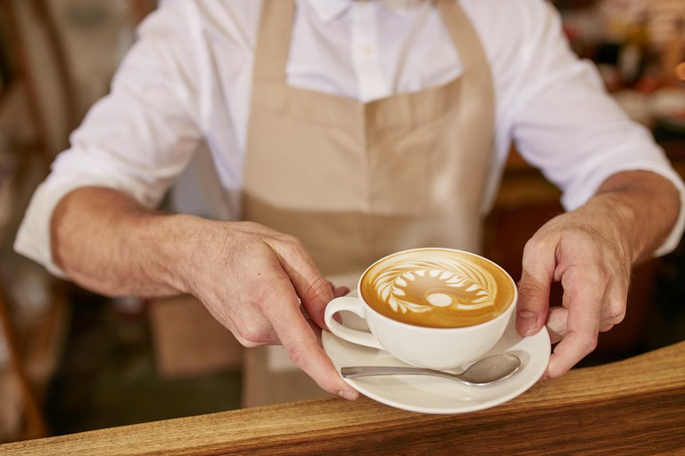 Close-up of man in apron serving coffee while standing in coffee shop.