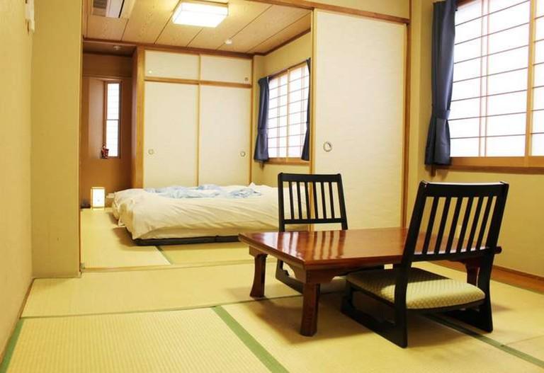 The rooms at Ryokan Kamogawa Asakusa feature tatami flooring and futon bedding