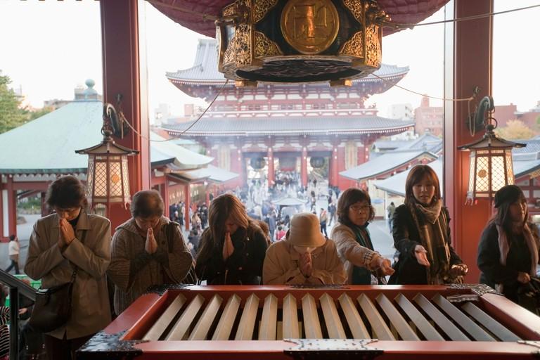 Worshippers in front of votive box at Senso-ji Temple, Shitamachi, Tokyo