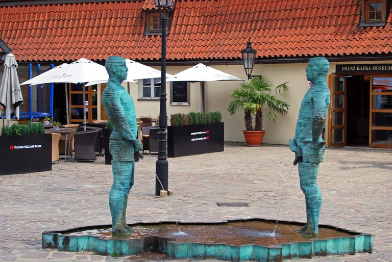 'Piss' by artist David Černý stands outside the Franz Kafka Museum