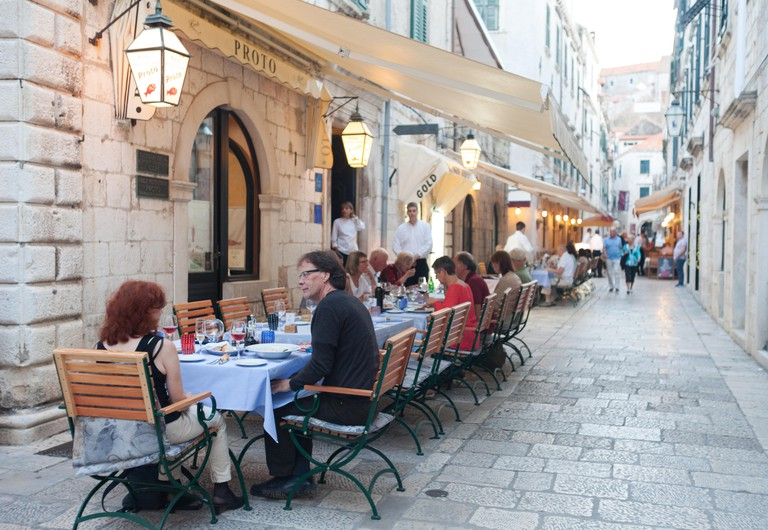 DUBROVNIK, CROATIA - MAY 28, 2014: Guests sitting at Proto restaurant terrace, one of Dubrovnik's best known places for fish spe