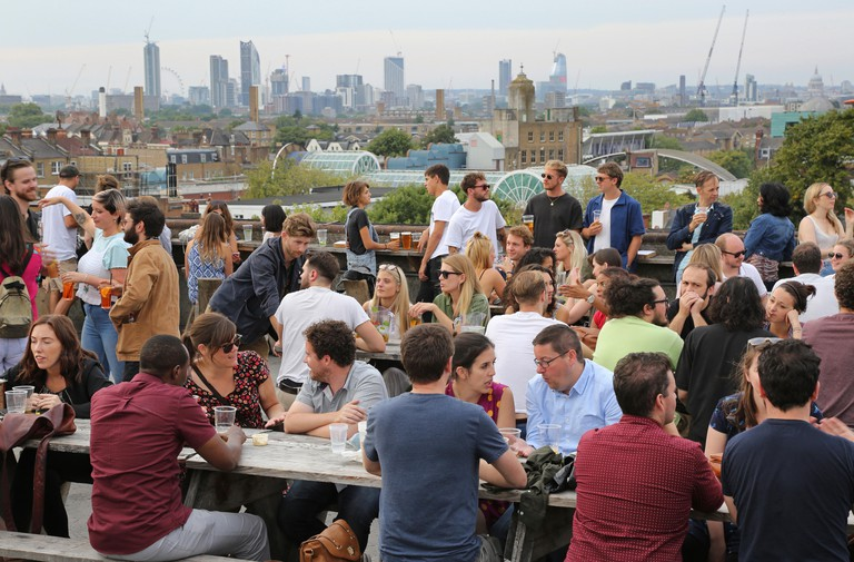 Customers at Frank's Cafe, the famous roof-top bar and restaurant on the multi-storey car park in Peckham, UK, overlooking the London skyline.