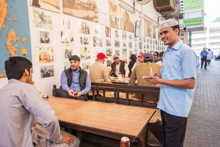 Waiter taking an order at an outdoor cafe in Manama, Bahrain.