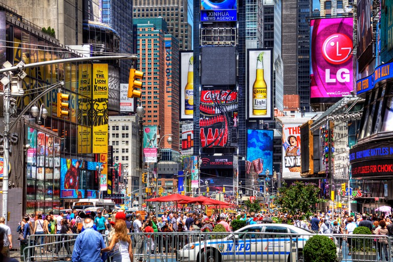 Busy Times Square in Manhattan, New York City, tourists, NYPD, bright lights advertising hoardings fill the scene modern cities