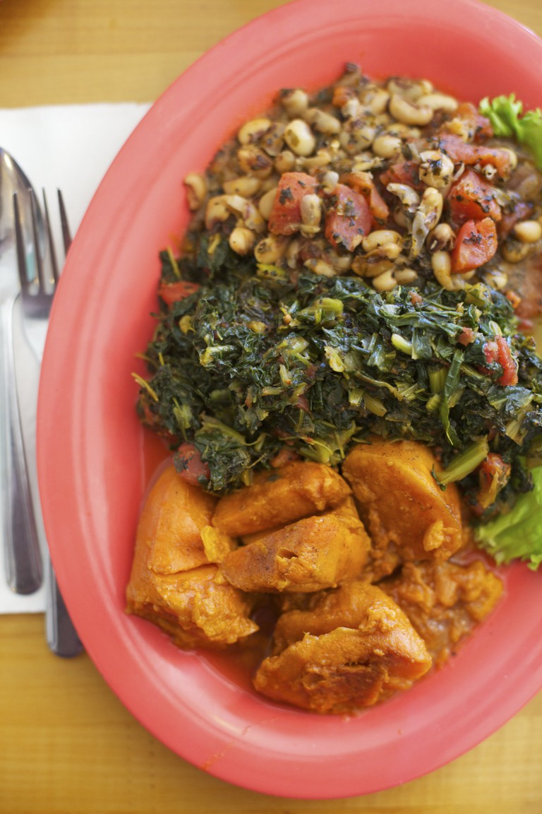 A healthy meal of vegan soul food, black-eyed peas, greens and sweet potatoes served on a bright salmon pink plate
