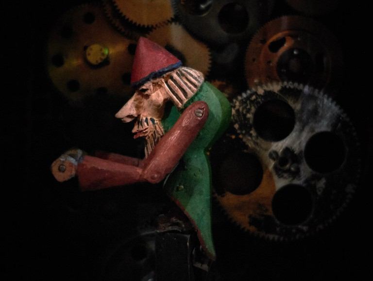Small animated wooden painted figure of a man holding a winch that turns a selection of gears in the background