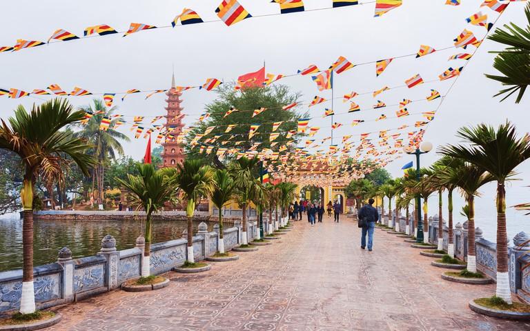 Hanoi, Vietnam - February 22, 2016: Bridge at West Lake and Temple in Tran Quoc Pagoda in Hanoi, Vietnam