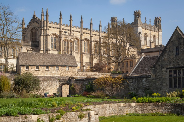 A gardener with a wheelbarrow attends to the Christ Church War memorial Garden with Christ Church Cathedral behind
